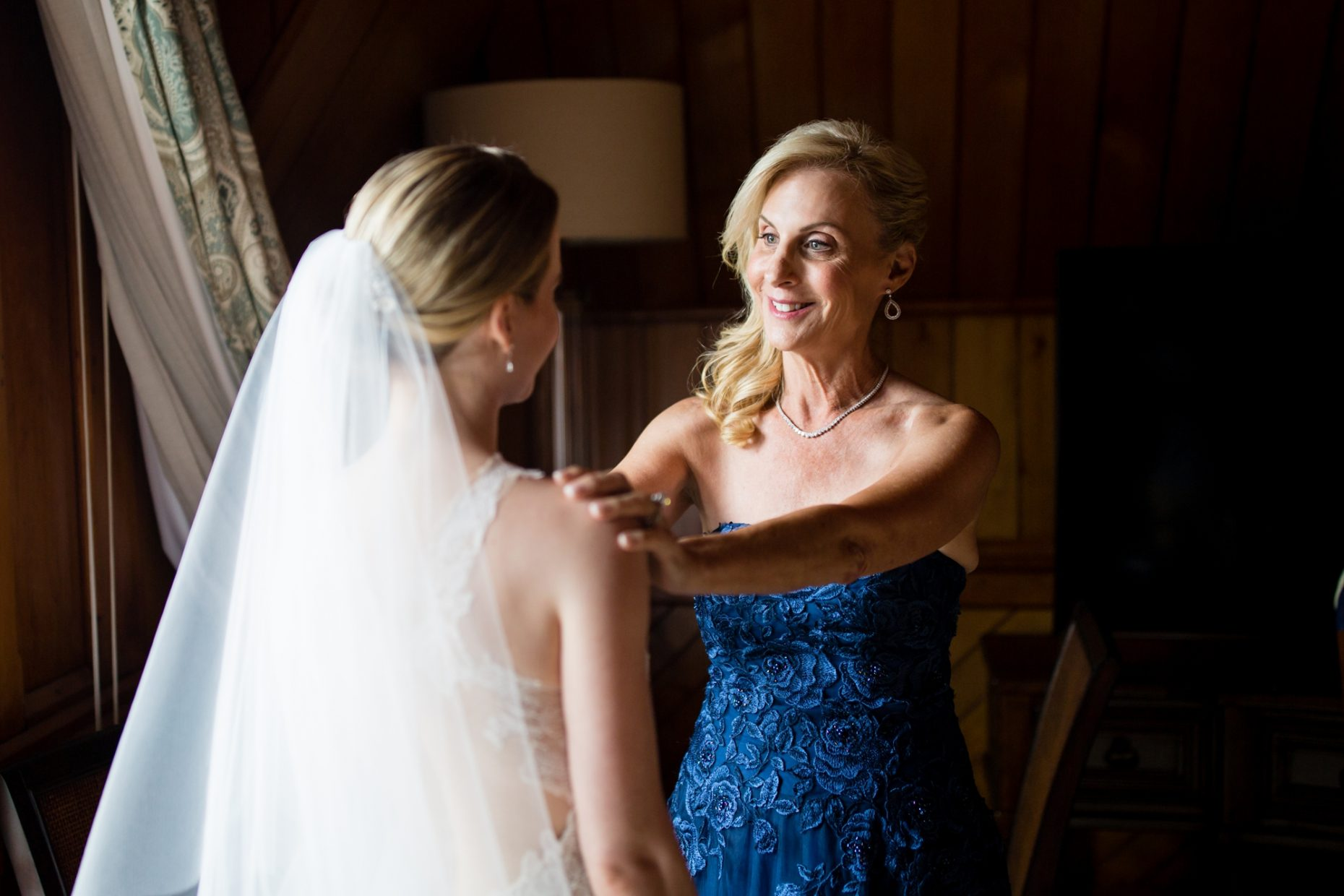 mother of bride helps bride get dressed on her wedding day