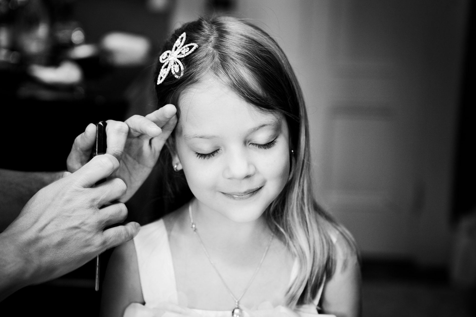 flower girl smiles as she gets her hair combed at castle hill inn