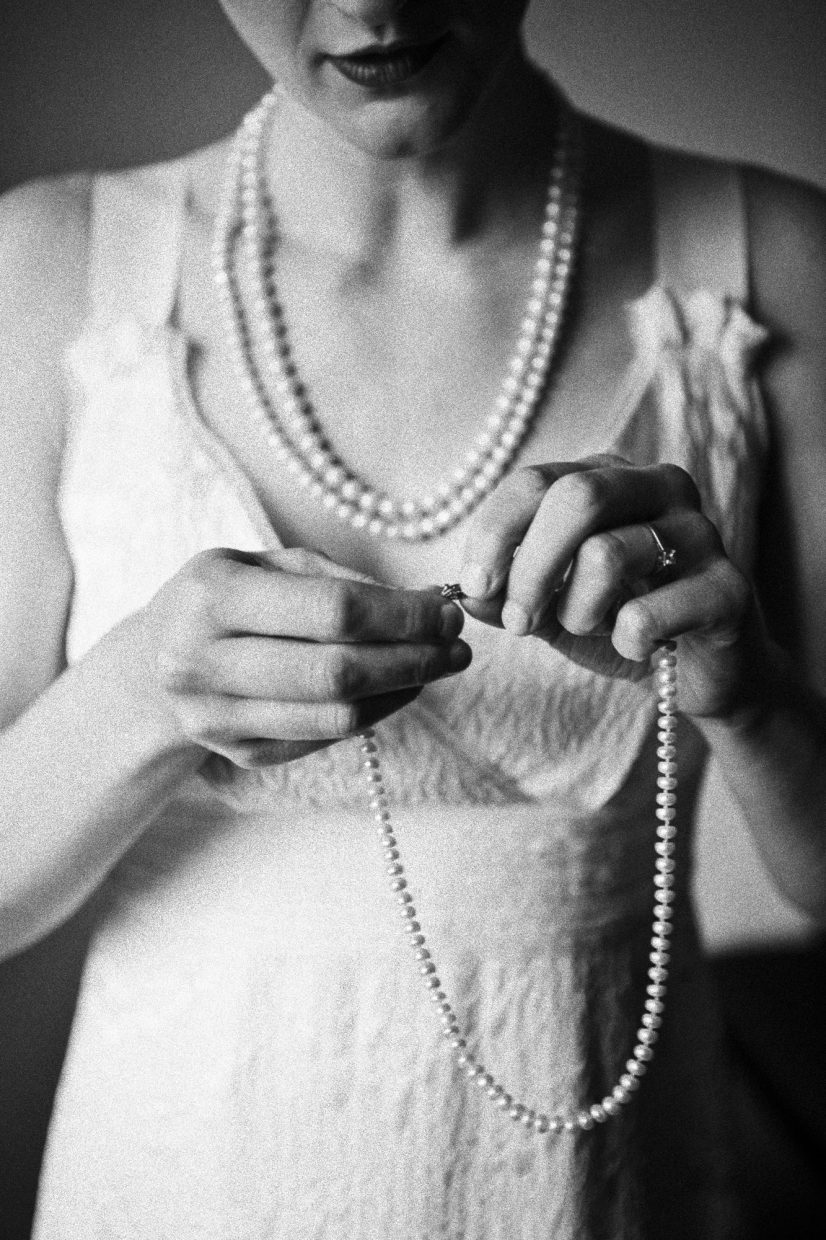classic black and white portrait of bride putting on her necklace in boston