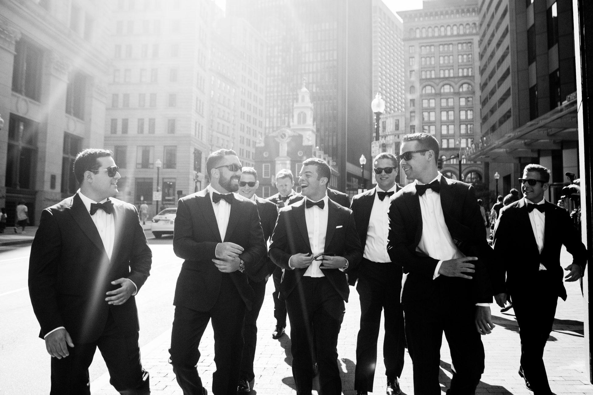 groom and groomsmen walk to a state room wedding
