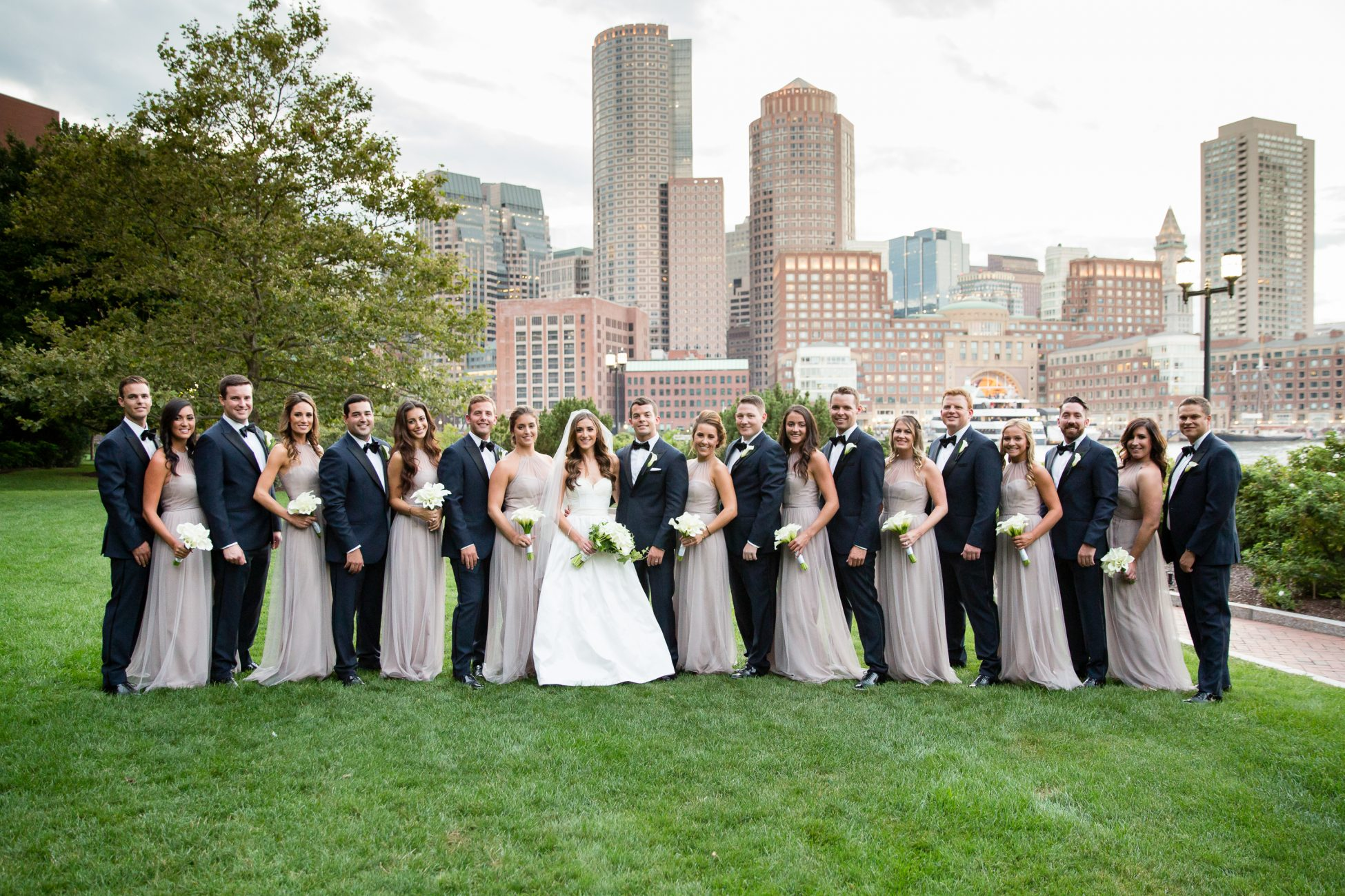 wedding party poses in front of the boston skyline at a state room wedding