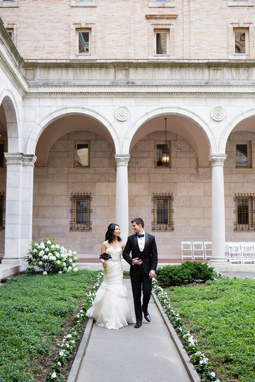 bride and groom walk through the mckim courtyard at the boston public library