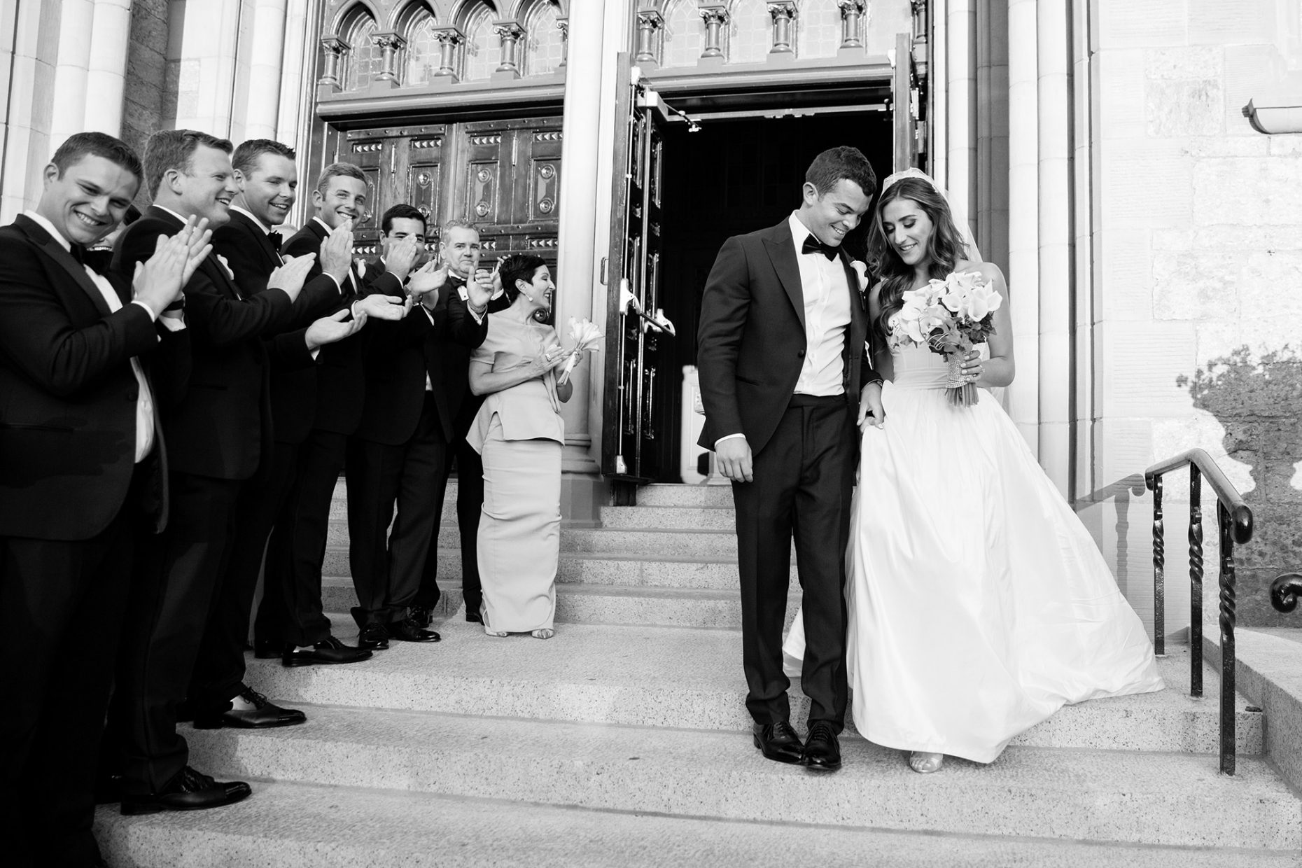 wedding party applauds as bride and groom exit boston ma church wedding ceremony