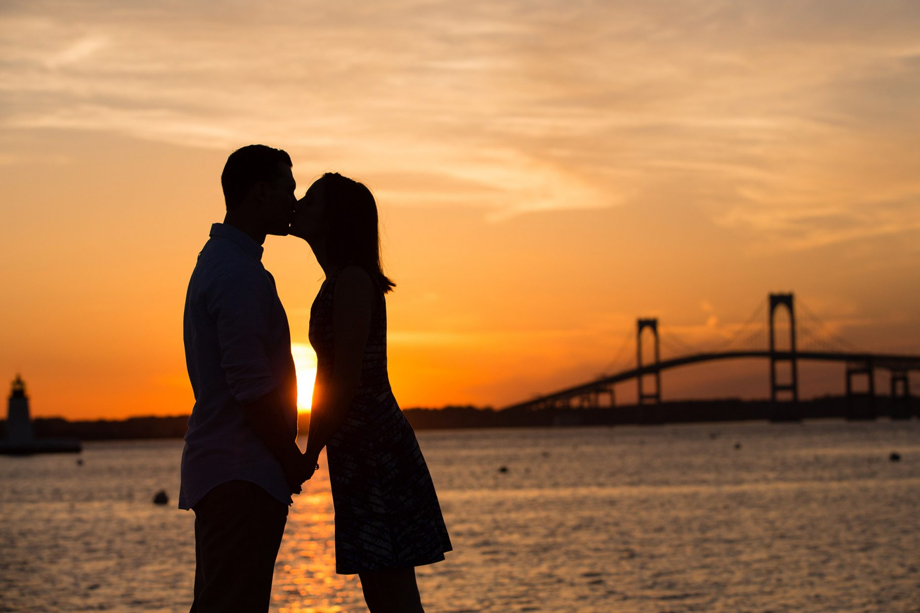 silhouette of couple in front of jamestown bridge in newport rhode island
