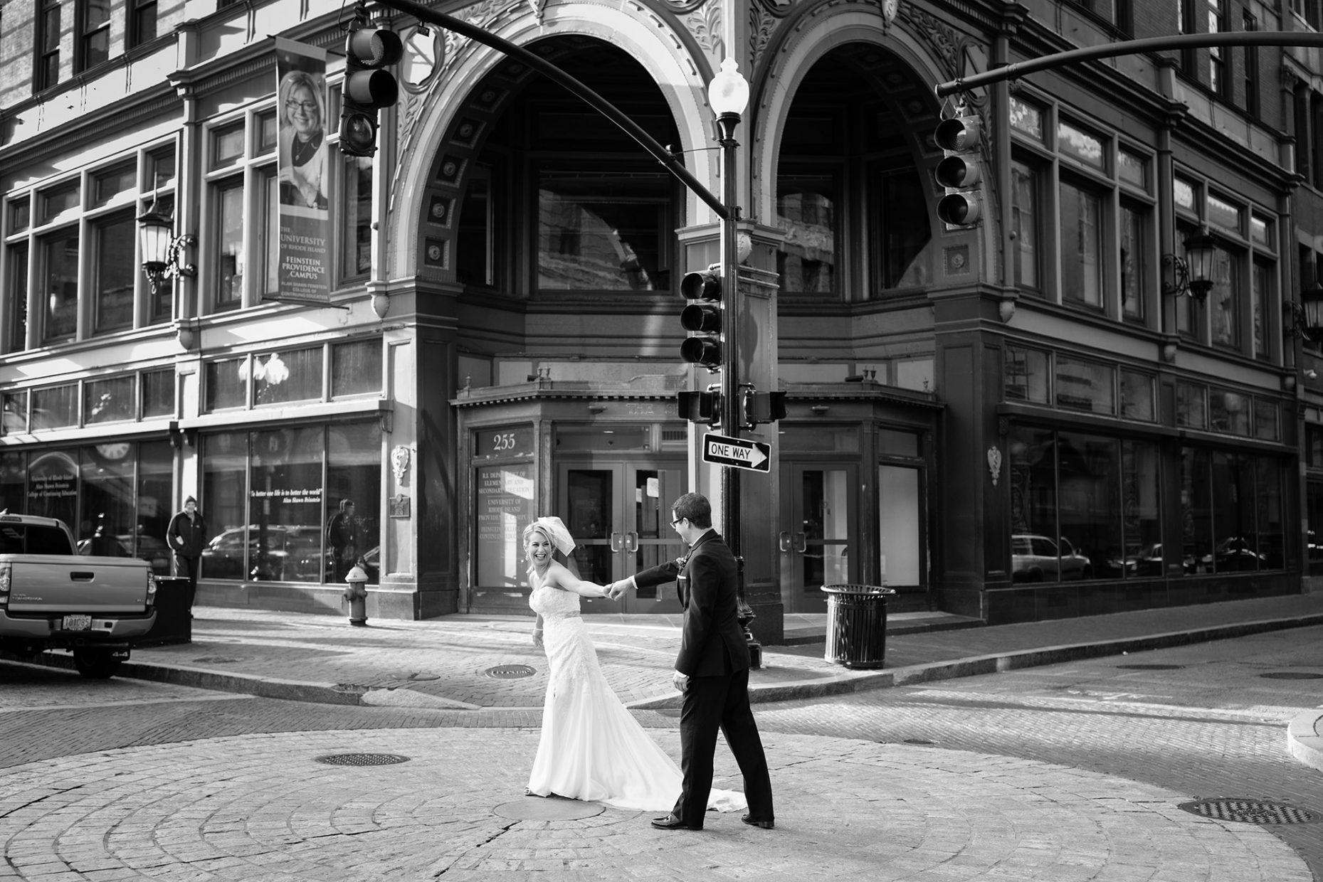 bride and groom walk through the streets after their wedding ceremony in providence rhode island