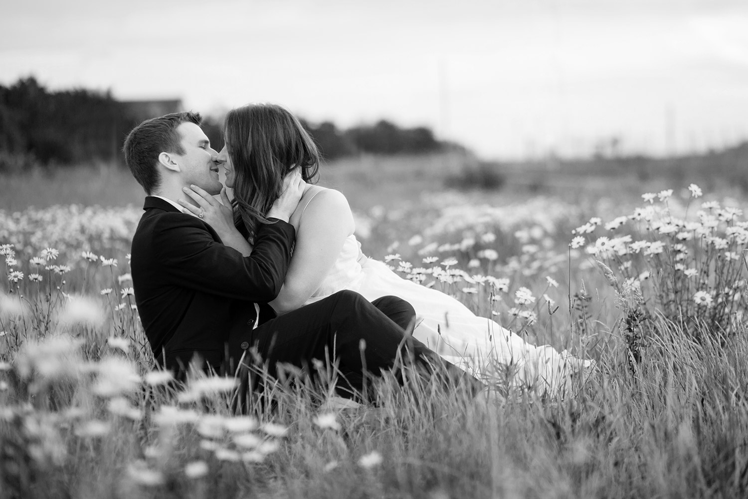 couple sits in a flower field and kisses during nantucket engagement photos