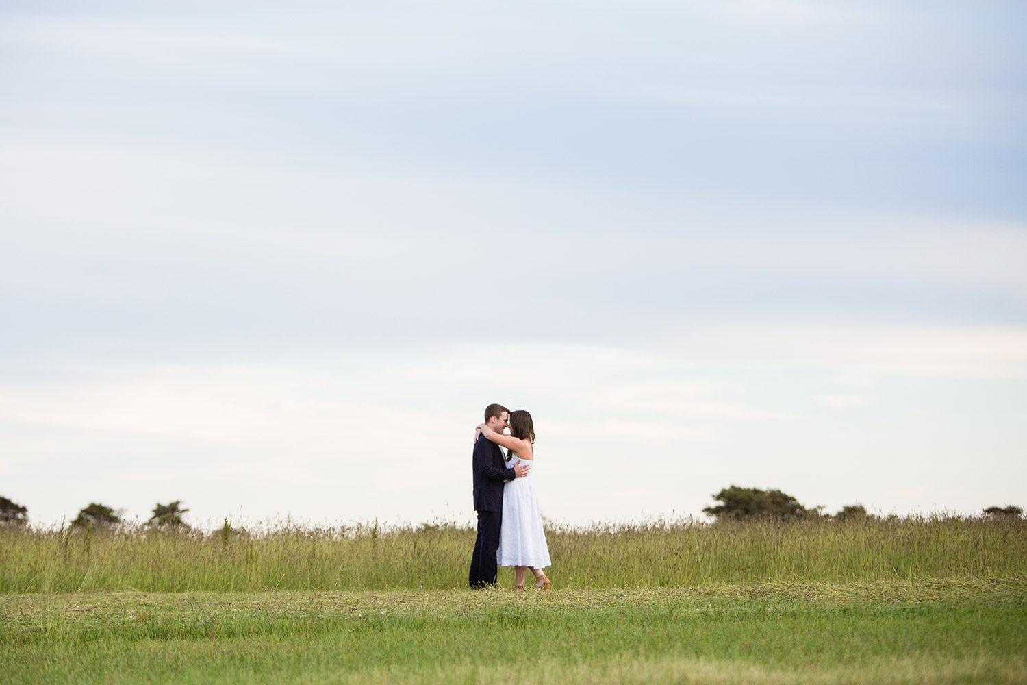 engaged couple kisses in a field on nantucket island in massachusetts