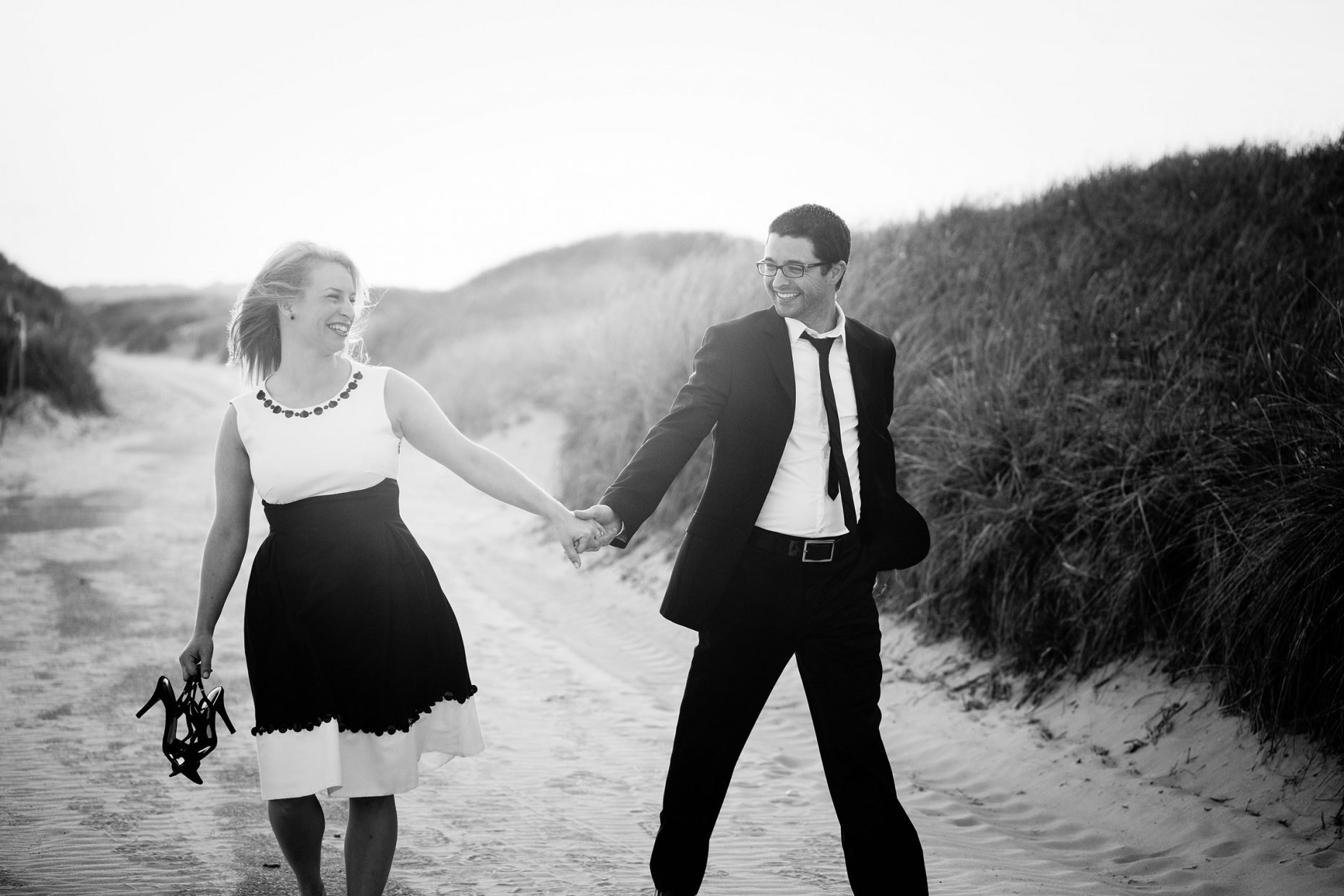 couple walks through sand dunes at horseneck beach in westport ma