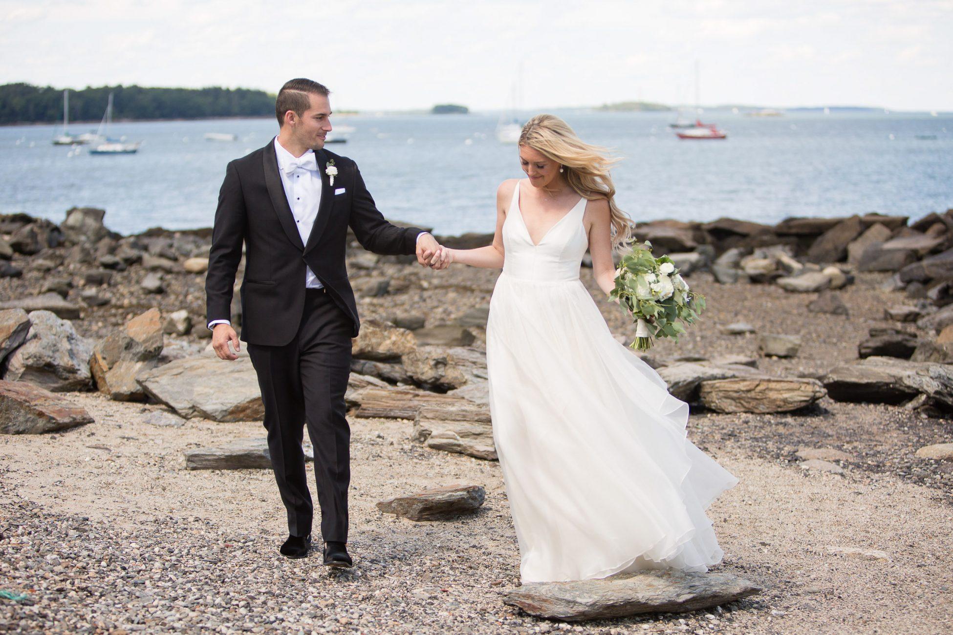 couple walks on rocky maine beach
