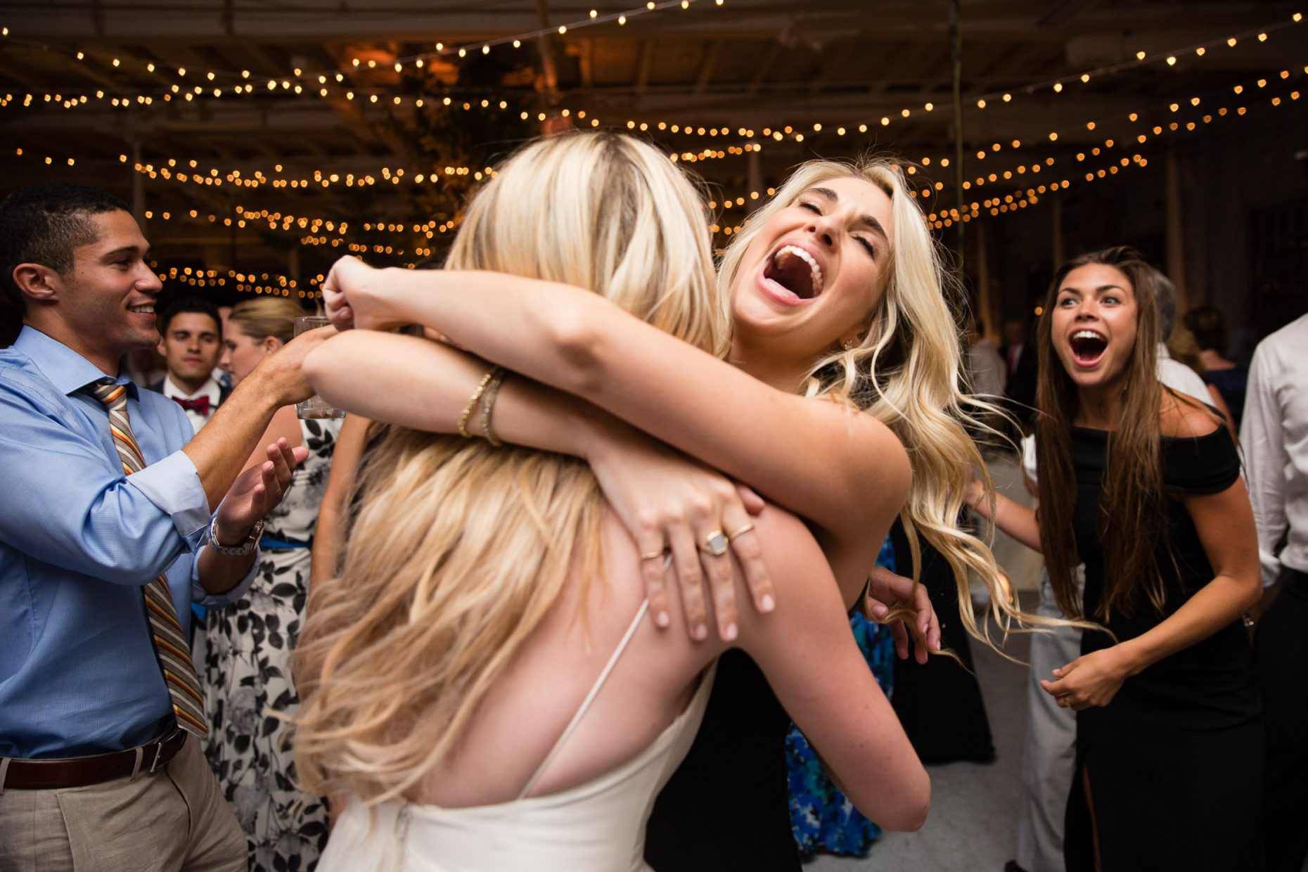 bridesmaid hugs bride on dance floor at portland company complex