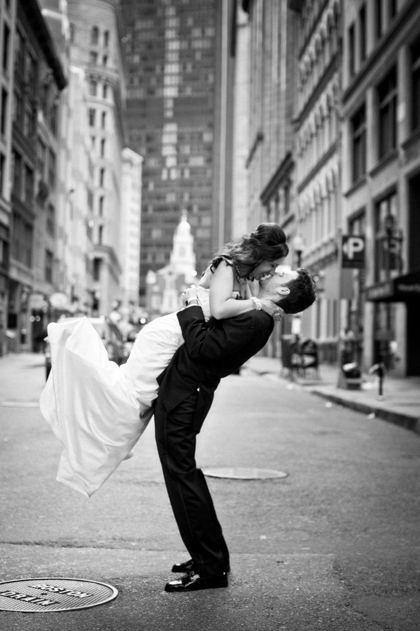 groom lifts bride on state street in boston ma