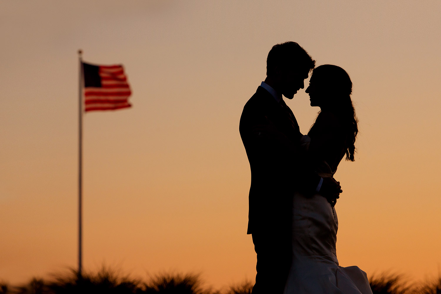 bride and groom silhouette with american flag at wychmere wedding on cape cod