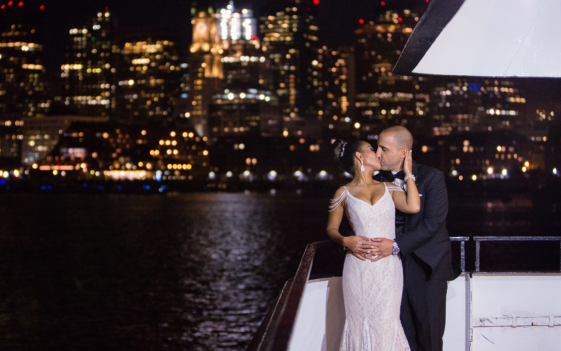bride and groom kiss in front of the night boston harbor skyline at their harbor cruise wedding