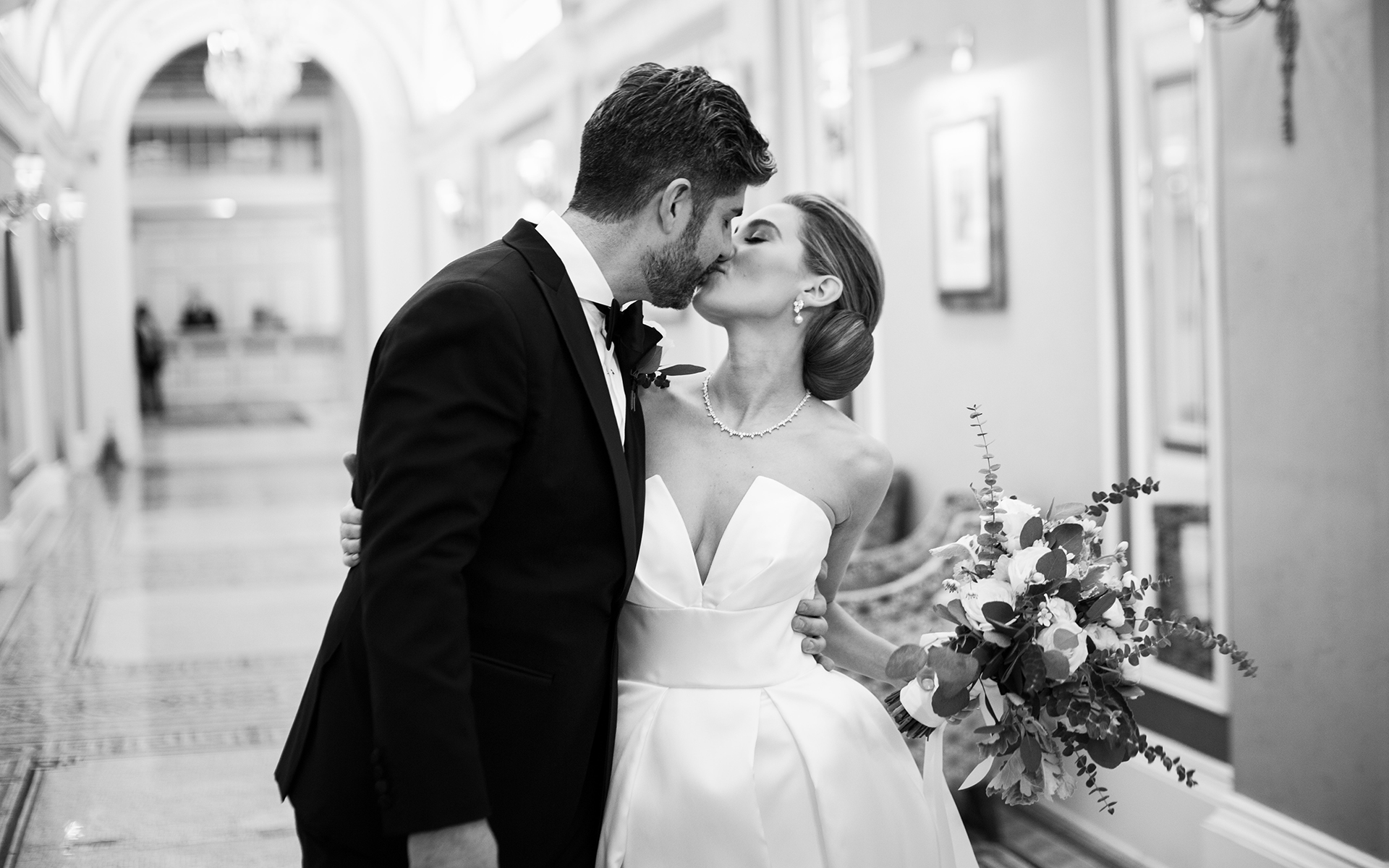bride and groom kiss at peacock alley at the fairmont copley plaza