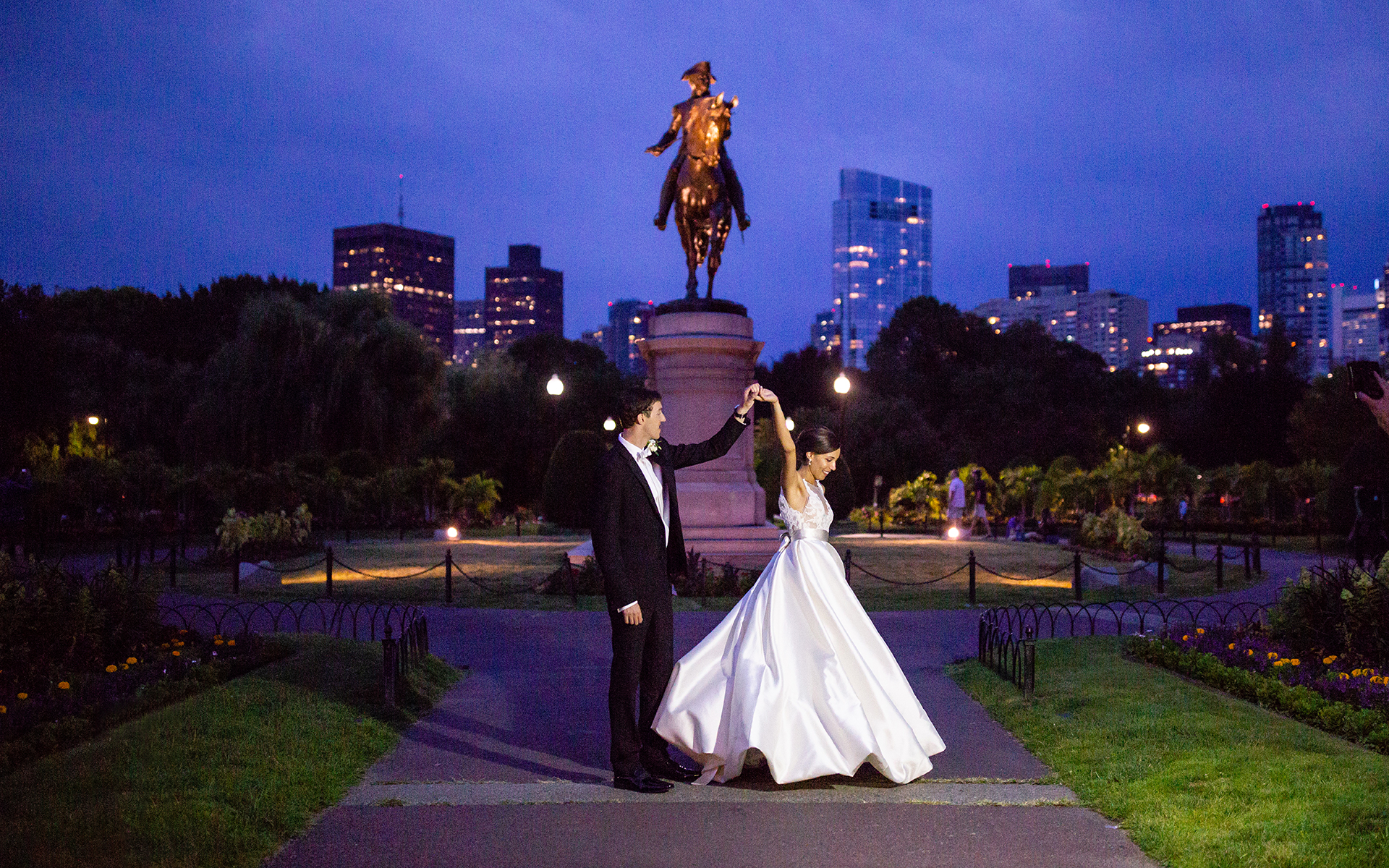 bride and groom dance at night in the boston public garden