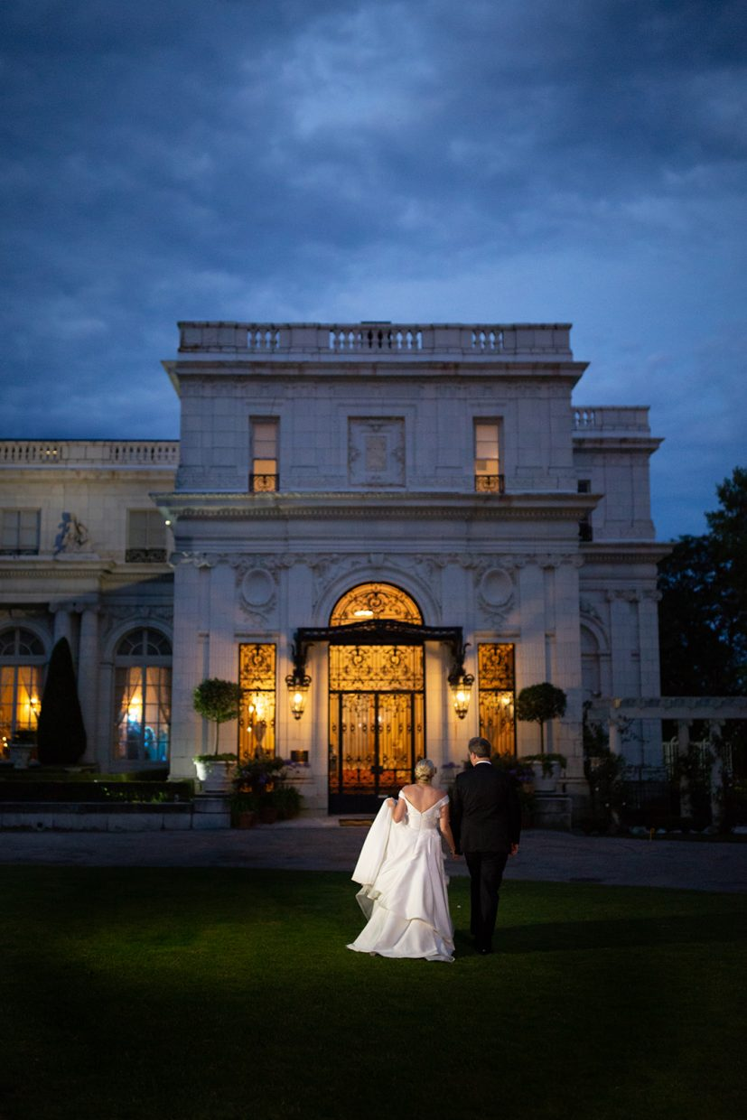 bride and groom walking towards rosecliff mansion in newport ri