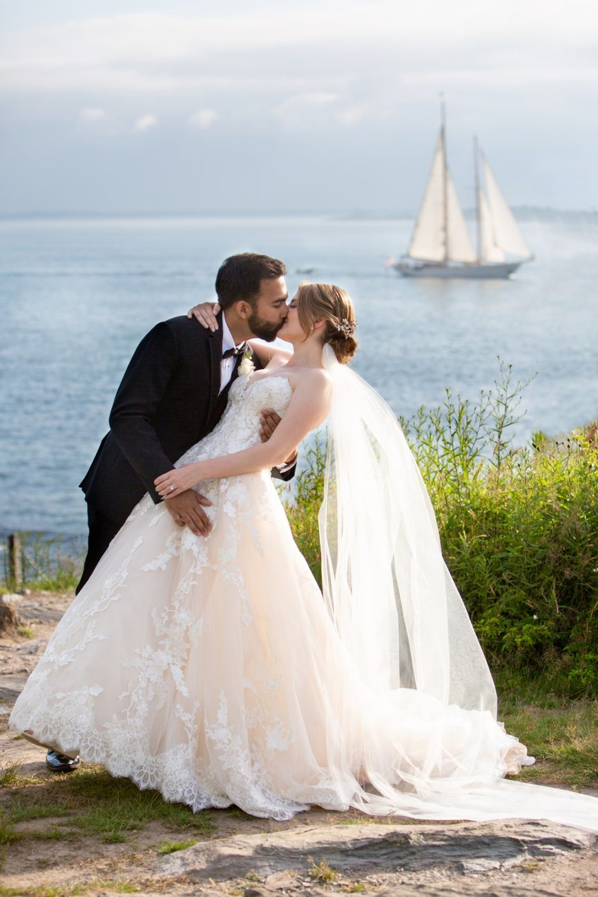 bride and groom at castle hill in lighthouse with sail boat
