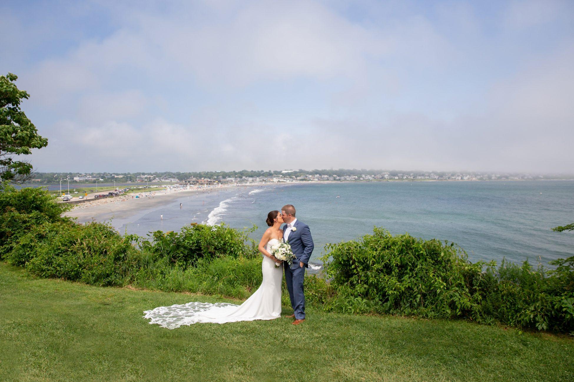 bride and groom kiss on the cliff walk in newport rhode island near the newport beach house