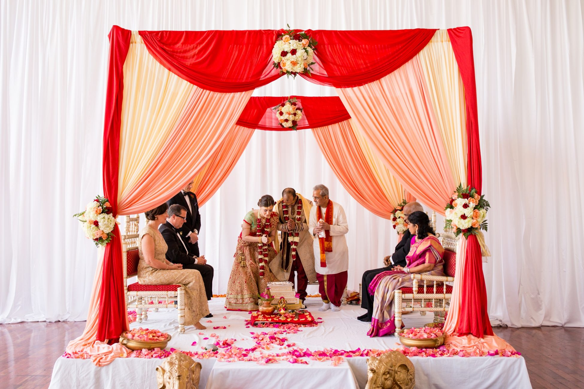 bride and groom bow at the end of their indian wedding ceremony at the state room